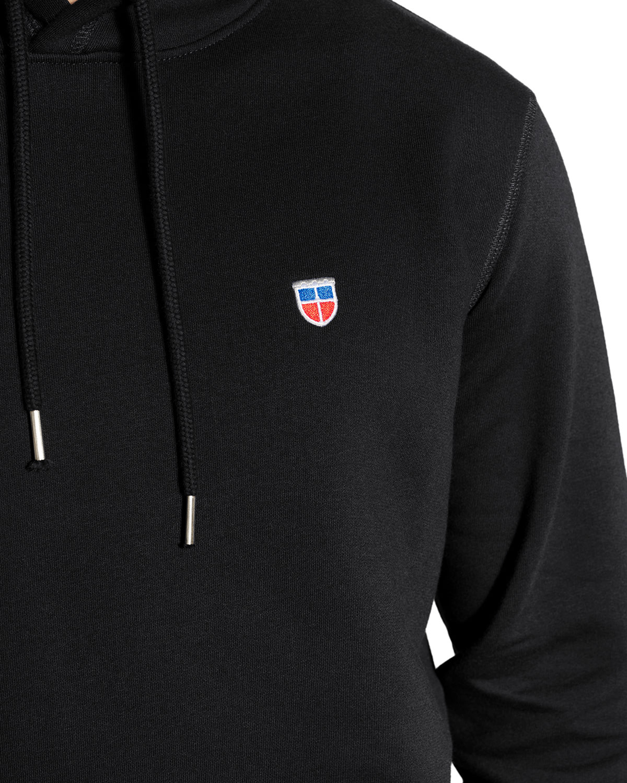 """Detail-Ansicht des Wappen-Sticks des hochwertigen und sportlich dünnen Herren Hoodie """"LUKAS"""" in der Farbe Schwarz von der Saarland Marke La sarre mit dem LASARRE Wappen in Blau, Weiß, Rot vorne auf der linken Brust und dem blauen LASARRE Markenzeichen am Saum und im Nacken"""